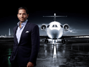 Business person in suit in front of private jet