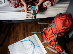 Traveler with a backpack, map and guidebook