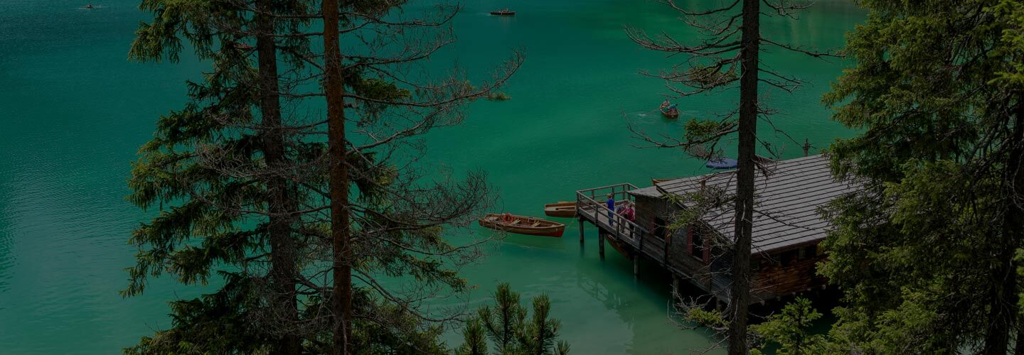 Cabin and row boats on an emerald green lake