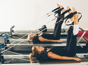 Women using pilates exercise equipment