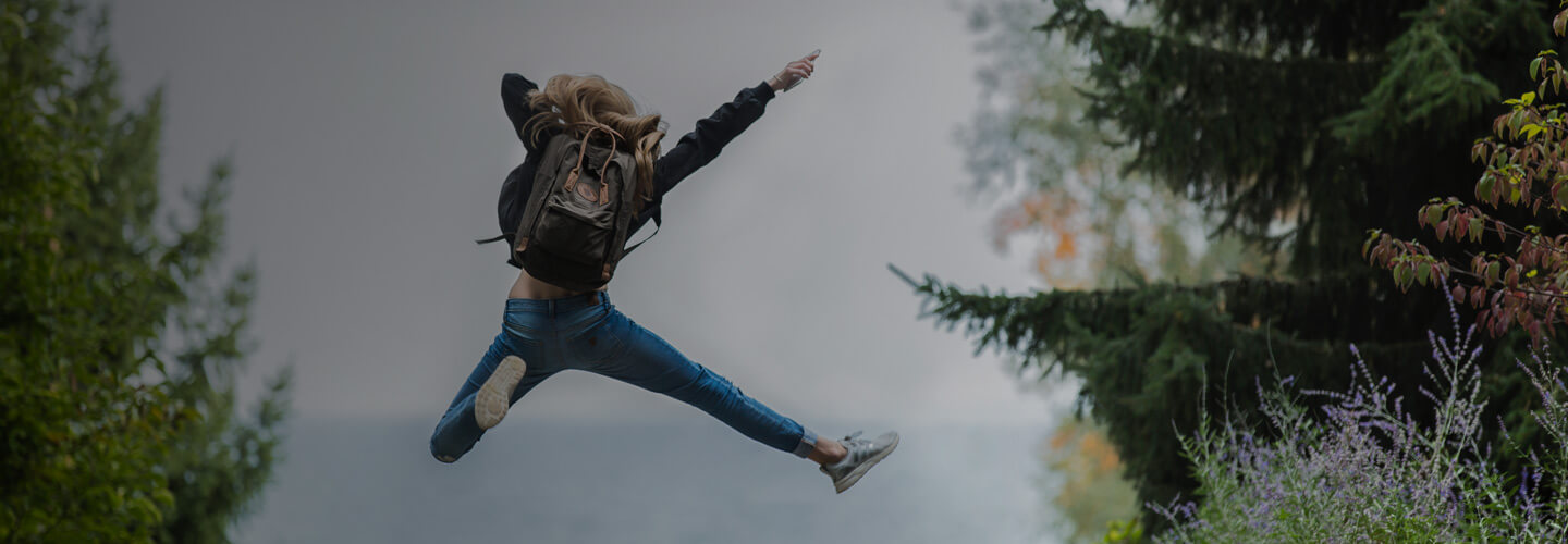 Woman with backpack jumping in excitement