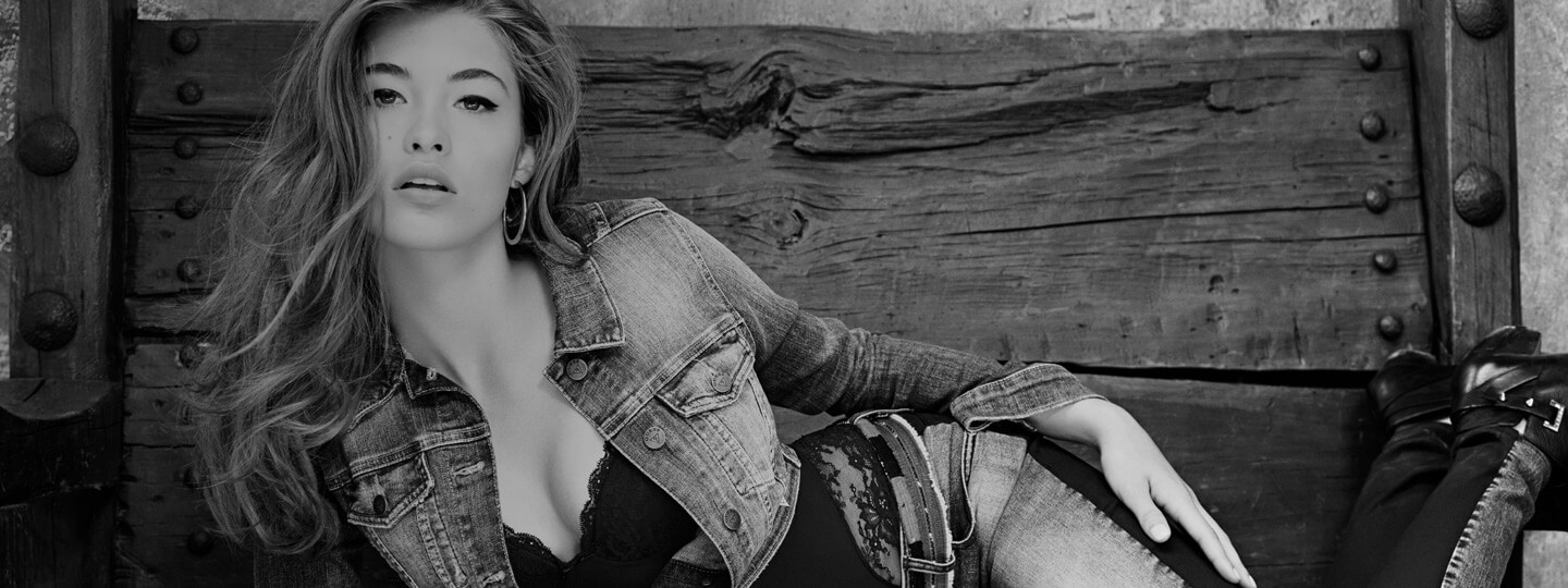 Black and white image of woman in an unbuttoned GUESS denim jacket